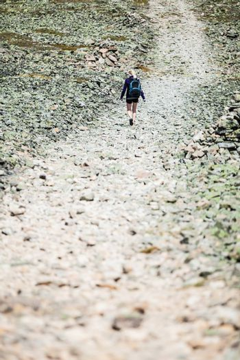 Young Woman Walking on a Rocky Hiking Path
