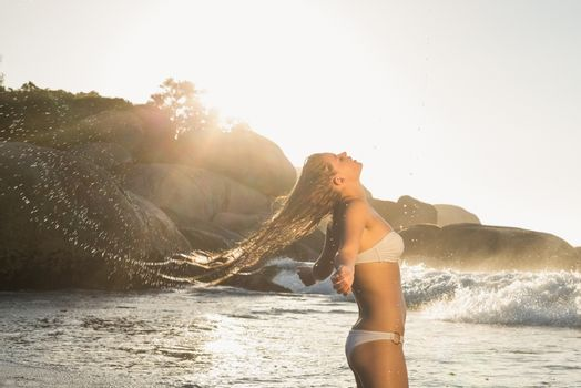 Beautiful blonde in white bikini at the beach tossing wet hair