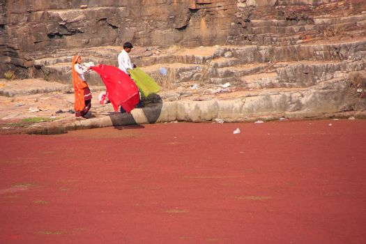 Indian women in colorful saris standing at the edge of red pond,
