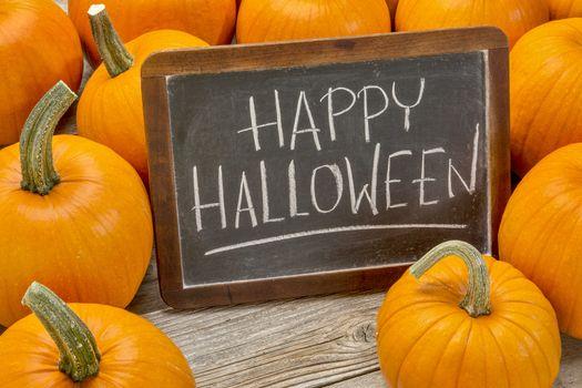 Happy Halloween - white chalk handwriting on a vintage slate blackboard surrounded by pumpkins