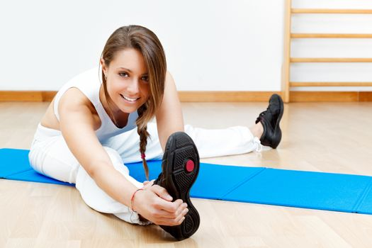 fit young female stretching on the floor sitting on mat
