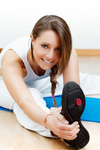 happy young female stretching on the floor sitting on mat