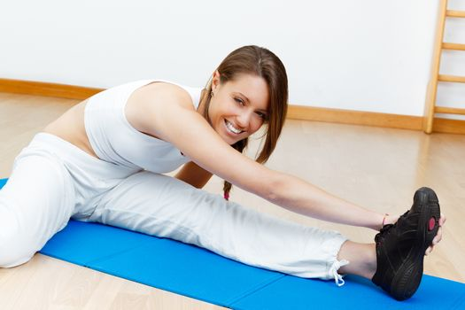 young female stretching on the floor sitting on mat