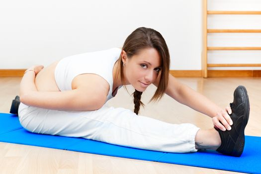 beautiful brunette female stretching on the floor sitting on a m