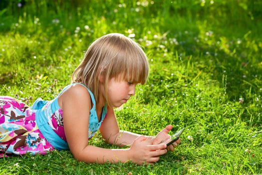 Child with a tablet computer outdoor