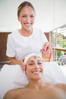 Smiling brunette getting micro dermabrasion