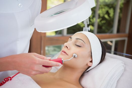 Peaceful brunette getting micro dermabrasion from beauty therapist