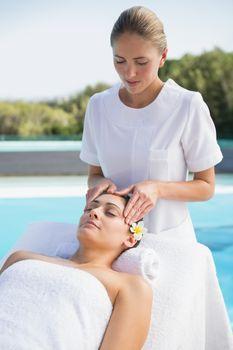 Tranquil brunette getting a head massage poolside