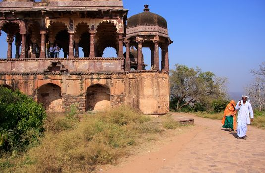 Indian man and woman walking along old temple, Ranthambore Fort,