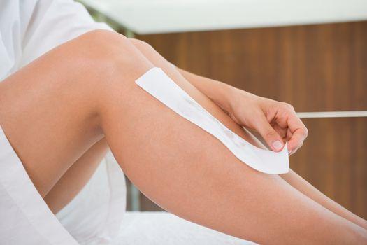 Woman waxing her legs herself