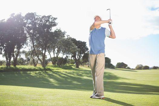 Golfer swinging on the grass