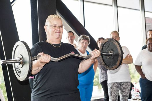 AMERSFOORT, THE NETHERLANDS - SEPTEMBER 13, 2014: Dutch grand prix strict curl at Amersfoort, the Netherlands on september 13, 2014. Female participant performing the strict curl setting a world record at sixty years of age.
