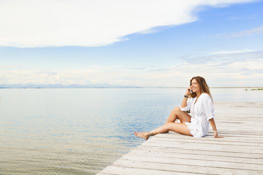 Smiling beautiful young woman sitting on a pier and talking on t