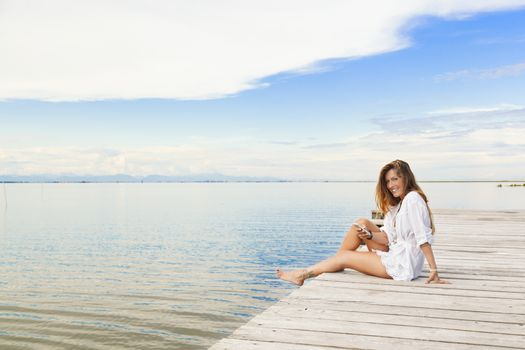 Smiling beautiful young woman sitting on a pier and using a mobi