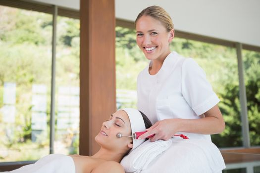 Brunette getting micro dermabrasion with therapist smiling at camera