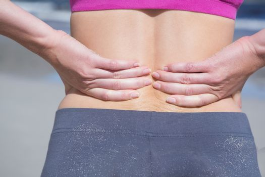 Fit woman touching her sore back