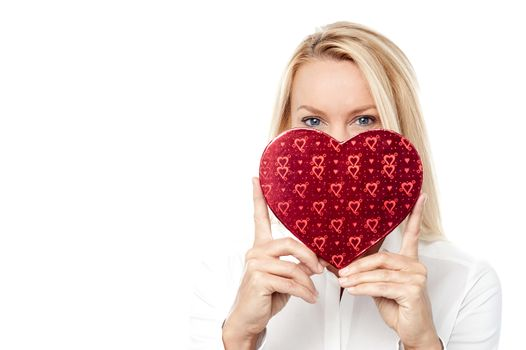 Woman holds a heart shape to her face