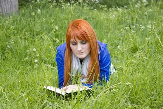 Young woman with red hair reading a book