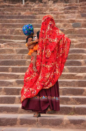 Indian women in colorful saris with a kid walking up the stairs