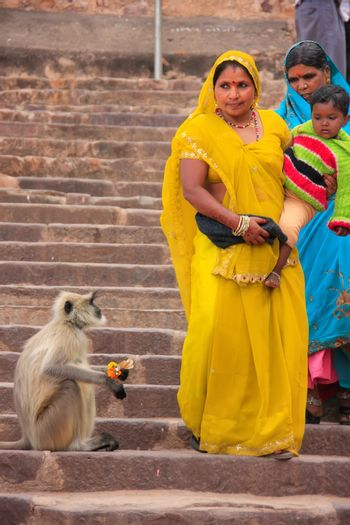 Indian women in colorful sari with a kid walking down the stairs