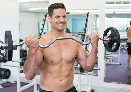 Shirtless smiling bodybuilder lifting heavy barbell weight  at the gym