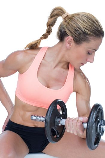Strong woman doing bicep curl with large dumbbell