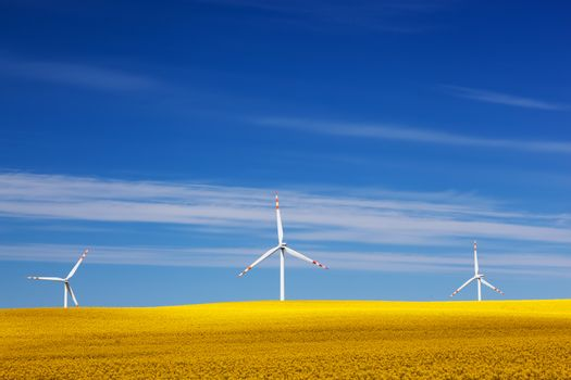 Wind turbines on spring field. Alternative, clean and natural source of energy