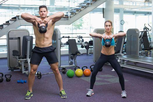 Bodybuilding man and woman lifting kettlebells