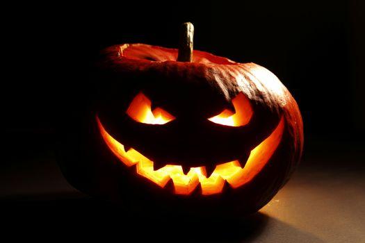 Evil smiling glowing halloween pumpkin on dark background
