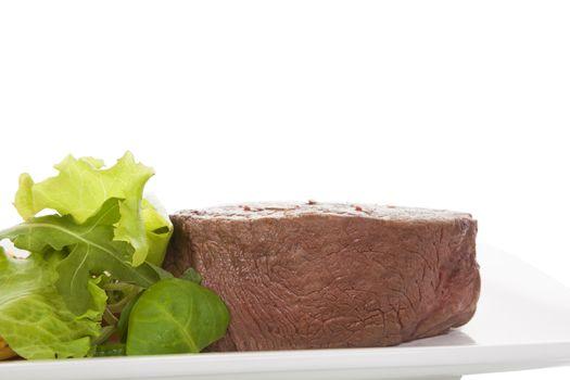 Big steak with salad.