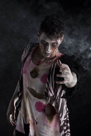Male zombie standing on black smoky background