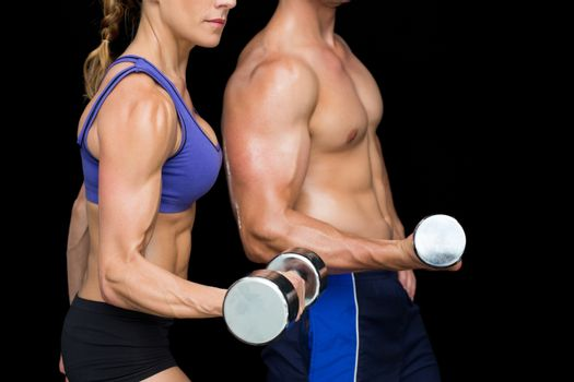 Bodybuilding couple posing with large dumbells
