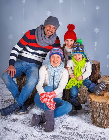 Winter Fashion. Happy family in winter hat, gloves and sweater in studio.
