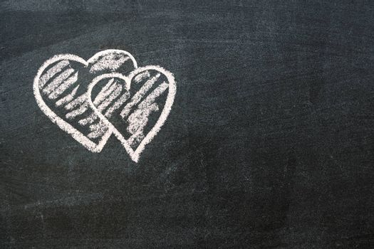 hand-drawn hearts symbols on the blackboard with blank space on left