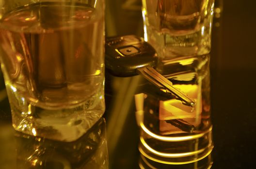 two whiskey shots on the bar shelf with car key between them; focus on key