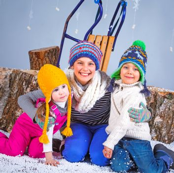 Winter Fashion. Adorable happy boy and girls in winter hat, gloves and sweater in studio.