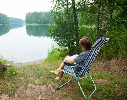 Boy sitting in deckchair reading a book on a lake shore