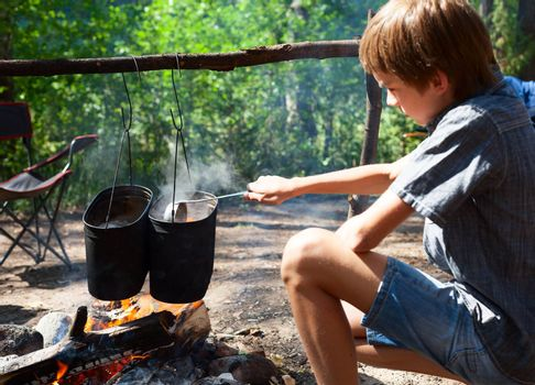 Young boy cooking camp food in cauldron on open fire