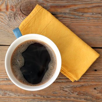 Coffee in a cup with yellow napkin