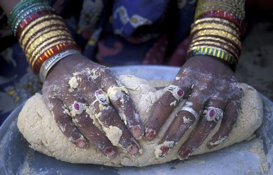 a women is making Bread in the town of Jaisalmer in the province of Rajasthan in India.