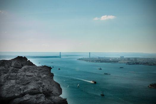 Large rock overlooking harbour with bridge