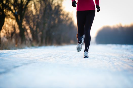 Winter running - Young woman running outdoors on a cold winter day