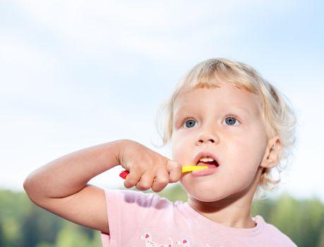 Portrait of cute little girl  brushing teeth  outdoor