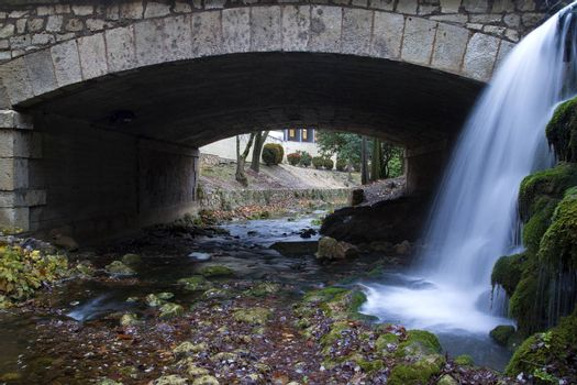 Little bridge made of stones in Cuenca, Spain, with a beautiful waterfall at is side.