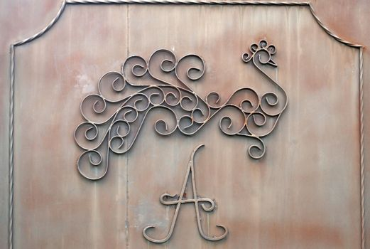"""Detail of iron gates with  letter """"A"""" and image of bird"""