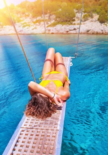Sexy woman tanning on sailboat