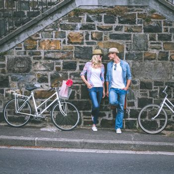 Hip young couple standing by brick wall with their bikes on a sunny day in the city