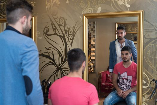 Handsome Young Hairdresser Giving A New Haircut To Male Customer At Parlor