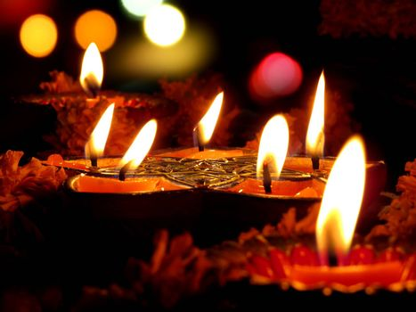 Beautiful lamps surrounded with flowers for a traditional ritual during Diwali festival
