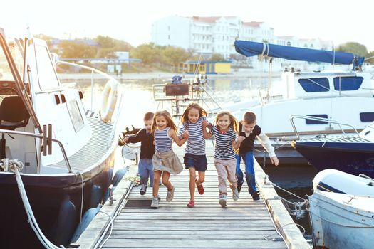 Group of many fashion kids wearing striped navy clothes in marine style running in the sea port